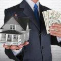 Mężczyzna z plikiem pieniędzy i modelem domu