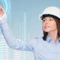 Kobieta w kasku przed interaktywnym ekranem