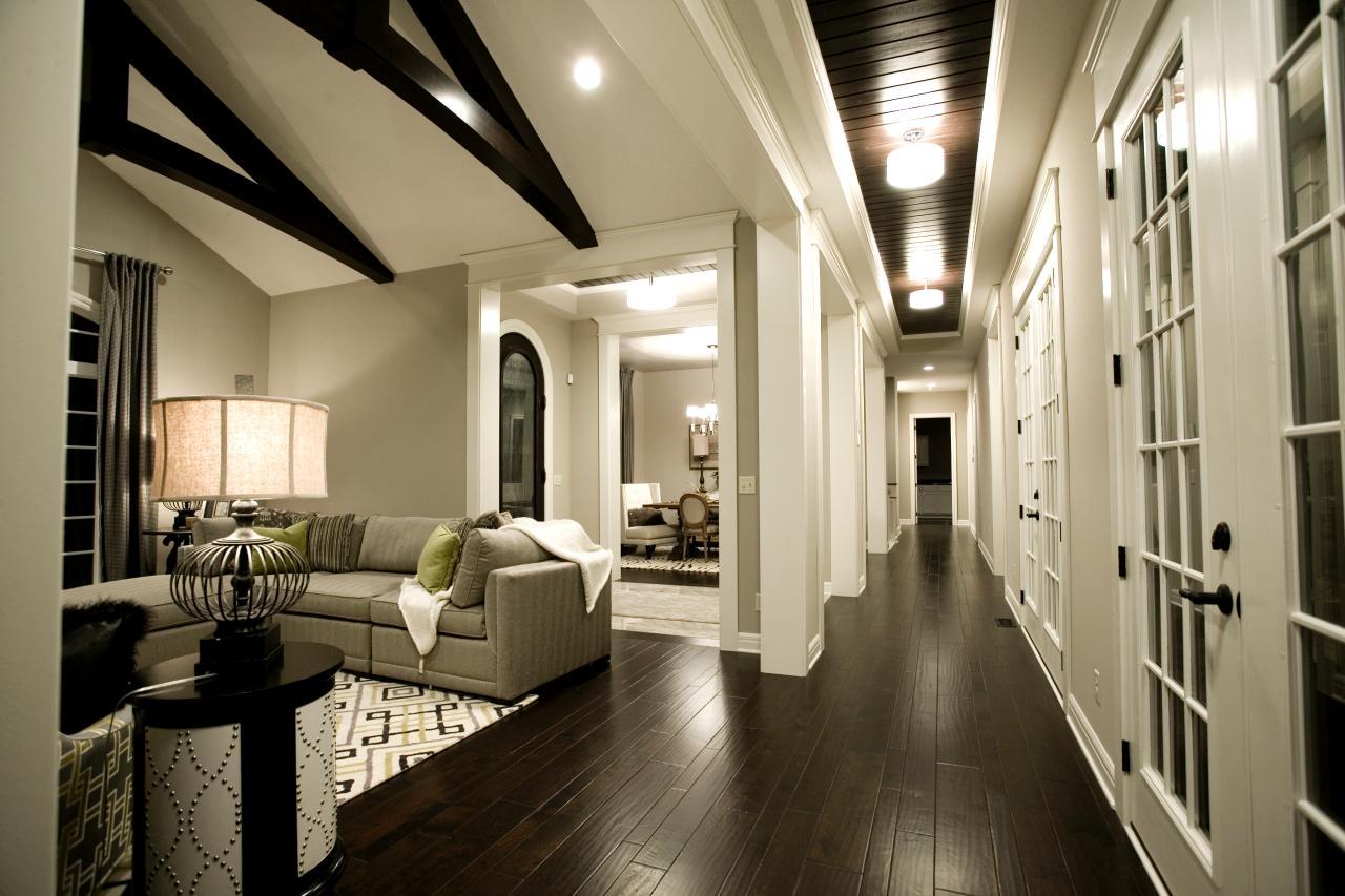 Wnętrze z bardzo ciemną podłogą, białymi ścianami i jasnymi meblami