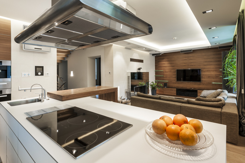 Salon z kuchnią oddzielony wyspą kuchenną i kanapą